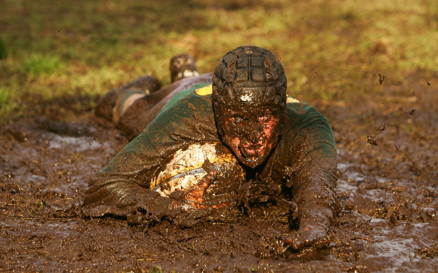 A rugby player slides on a muddy field Sport,Dirty,Mud,Jersey,Football,Rugby,Sportswear,Playing,Adult,Sweat,grass,rugby union,rugby league,rough,ball,compete,try,slop,filth,head gear,skull cap, mouth guard,slide